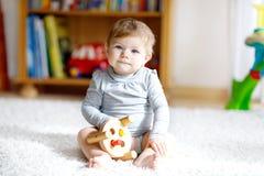 Neonata adorabile che gioca con il giocattolo di legno educativo in scuola materna Fotografia Stock Libera da Diritti
