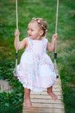 Neonata adorabile che gode di un giro dell'oscillazione su un campo da giuoco in un parco fotografia stock