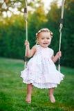 Neonata adorabile che gode di un giro dell'oscillazione su un campo da giuoco in un parco Fotografie Stock