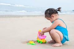 Neonata asiatica che gioca con la sabbia sulla spiaggia Immagini Stock Libere da Diritti