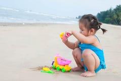 Neonata asiatica che gioca con la sabbia sulla spiaggia Immagine Stock