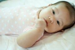 Neonata asiatica che mette su letto immagine stock libera da diritti