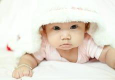 Neonata asiatica che mette su letto fotografie stock