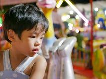 Neonata asiatica che prende una rotonda/carosello ad una fiera immagini stock