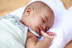 Neonata asiatica che succhia il suo pollice Immagini Stock