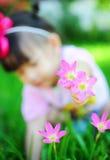 Neonata asiatica con il fiore immagini stock
