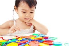 Neonata asiatica del primo piano che gioca infilando la linea Toy Isola dei bottoni Fotografia Stock