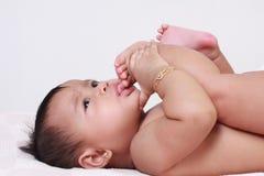 Neonata asiatica sveglia che succhia le sue dita del piede Fotografie Stock Libere da Diritti