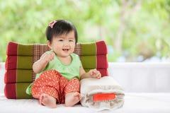 Neonata asiatica sveglia in vestito tailandese dal traditon che si siede con il cuscino Immagine Stock