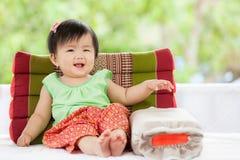 Neonata asiatica sveglia in vestito tailandese dal traditon che si siede con il cuscino Fotografia Stock