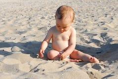 Neonata in buona salute che gioca con la sabbia sulla spiaggia immagine stock