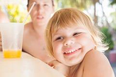 Neonata caucasica bionda sveglia sorridente con succo Fotografia Stock Libera da Diritti