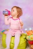 Neonata che beve un succo di mele Immagini Stock Libere da Diritti