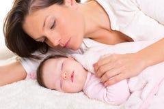 Neonata che dorme con la cura della madre vicino Fotografie Stock