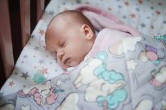 Neonata che dorme nel suo letto Immagini Stock