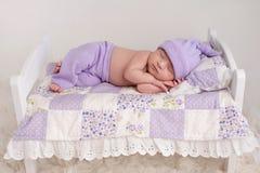 Neonata che dorme su un piccolo letto Fotografia Stock