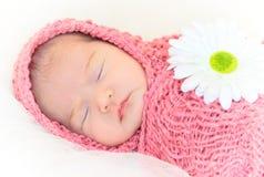 neonata che dorme sull'involucro rosa con il fiore immagine stock
