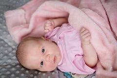 Neonata che esamina la macchina fotografica nel suo letto Fotografia Stock