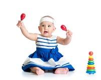 Neonata che gioca con i giocattoli musicali Fotografia Stock
