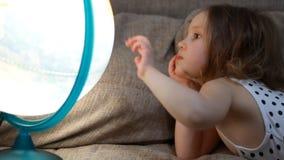 Neonata che gioca con il globo Il bambino studia la geografia e una mappa del mondo stock footage