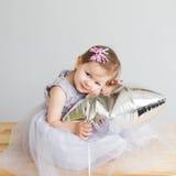 neonata che gioca con il pallone a forma di stella d'argento Immagine Stock