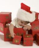 Neonata che gioca con le caselle di natale Fotografia Stock
