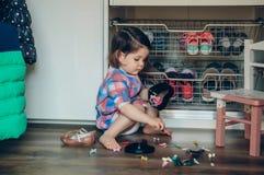 Neonata che gioca con le clip di capelli che si siedono nel Immagini Stock