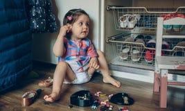 Neonata che gioca con le clip di capelli che si siedono nel Fotografie Stock Libere da Diritti