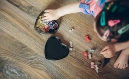 Neonata che gioca con le clip di capelli che si siedono nel Fotografia Stock