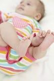 Neonata che gioca con le dita del piede Immagini Stock