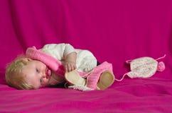Neonata che gioca con una sciarpa e un cappello Immagini Stock