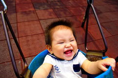 Neonata che gioca su un'oscillazione Fotografie Stock Libere da Diritti