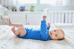 Neonata che indossa i vestiti blu che si rilassano nella camera da letto Immagini Stock Libere da Diritti