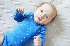 Neonata che indossa i vestiti blu che si rilassano nella camera da letto Fotografia Stock Libera da Diritti