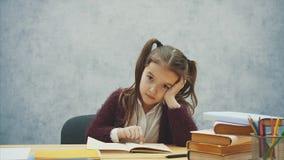 Neonata che legge un libro per sedersi su un interno grigio Scolara che studia il manuale Un bambino di un uniforme scolastico è archivi video