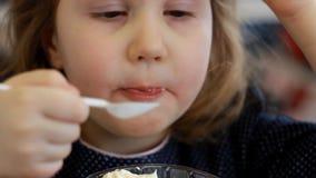Neonata che mangia dessert e che beve succo nel caffè Ritratto di un bambino che mangia il gelato archivi video