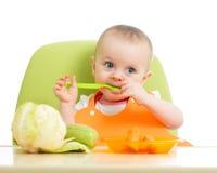 Neonata che mangia le verdure Immagini Stock