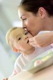 Neonata che mangia pranzo con sua madre che la aiuta Fotografia Stock Libera da Diritti