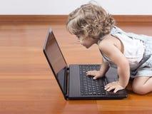Neonata che per mezzo di un computer portatile Immagini Stock Libere da Diritti
