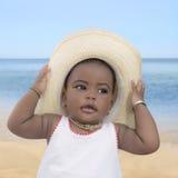 Neonata che porta un cappello di paglia alla spiaggia, nove mesi Fotografia Stock