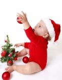 Neonata che porta un cappello di Santa Claus, giocante con le palle rosse, vicino all'albero di Natale Immagine Stock