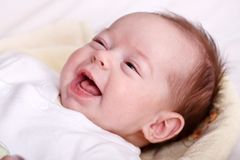 Neonata che ride con il sorriso senza denti Immagine Stock