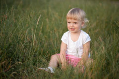 Neonata che si siede nell'erba Fotografia Stock