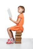 Neonata che si siede sui libri che leggono un libro Immagine Stock