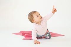 Neonata che si siede sul pavimento isolato sopra indicare bianco del fondo Fotografia Stock Libera da Diritti