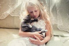 Neonata che si tiene per mano un gattino Fotografia Stock