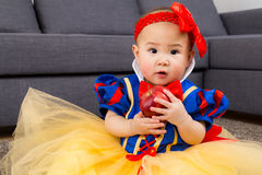 Neonata che tiene una mela con il condimento del partito fotografia stock