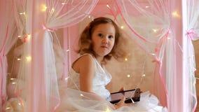 Neonata che utilizza compressa nella camera da letto Bambino che guarda un video su uno schermo di computer e che gioca nella sua stock footage