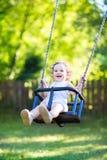 Neonata con capelli ricci che oscillano nel parco soleggiato Fotografia Stock