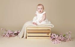 Neonata con Cherry Blossom Flowers nel vestito da primavera su Blanke Immagine Stock
